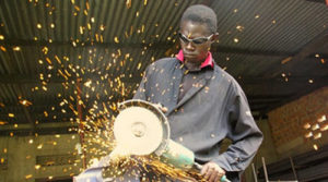 Worker using an angle grinder in a factory.