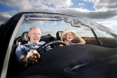 A couple driving in a car with excited faces.