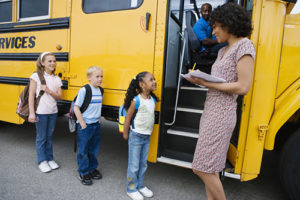 Teacher loading student onto a school bus
