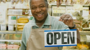 Man opening his store up by flipping the open sign