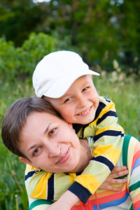 A lady smiling with a smiling kid on her back hugging her.