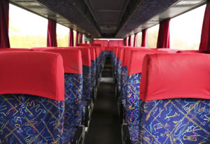 Interior shot of a charter bus focusing on seating.