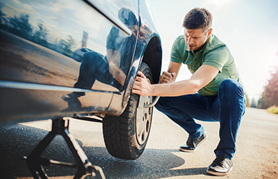 Man fixing car on side of road