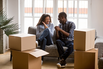 Couple sitting on the couch as they are unpacking their apartment.