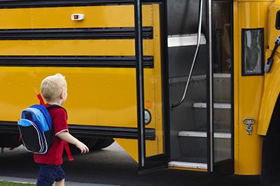 Teacher loading student onto a school bus