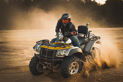 Individual riding an ATV out in the outdoors.